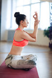 Portrait of young woman meditating in pose of lotus in isolation. Woman practicing advanced yoga against a bright wall Stock Image