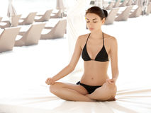 Portrait of young woman meditating in pose of lotus. Yoga backgr Royalty Free Stock Photography