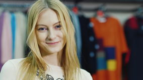 Portrait of young woman model looks at a clothing store. She smiles looking at the camera. HD video stock video footage
