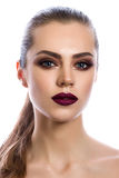 Portrait of young woman with modern makeup. Portrait of young woman with wine red lips and bronze smokey eyes. Modern fashion make-up. Studio shot. Ponytail Stock Image