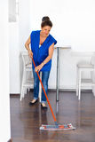 Portrait Of Young Woman Mopping Floor At Home . Cleaning Sevice.  Stock Photos