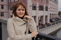 Portrait of young woman in Moscow, Russia. Modern buildings on the background. Portrait of young woman wearing a coat in Moscow, Russia. Modern buildings on the Royalty Free Stock Images