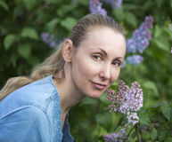 Portrait of the young woman near the blossoming lilac Stock Photo