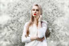 Portrait of young woman near blossoming tree. Red lips. Flowers spring Royalty Free Stock Photo