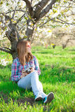 Portrait of young woman  near the tree. Portrait of young beautiful woman sitting near the blooming tree Stock Photo