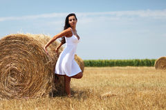 Portrait of a young woman next to haystack. Cute girl standing near a rolled haystack and leaning on it Royalty Free Stock Images