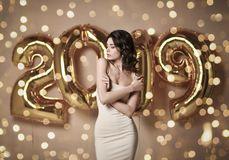 Portrait of a young woman in nude dress s Under boke Having Fun With Gold 2019 Balloon. Portrait of a smiling young shy woman in nude dress showing gift box and royalty free stock photography