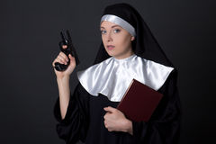 Portrait of young woman nun with bible and gun over grey Stock Images