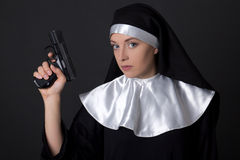 Portrait of young woman nun with gun over grey Stock Photo