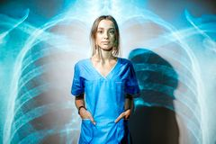 Nurse on the x-ray of human lungs background. Portrait of a young woman nurse in uniform with projected x-ray of human lungs Stock Photo