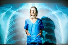 Nurse on the x-ray of human lungs background. Portrait of a young woman nurse in uniform with projected x-ray of human lungs Royalty Free Stock Images