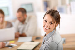 Portrait of young woman at office with coworkers Royalty Free Stock Images