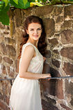 Portrait of young woman by old stone wall Royalty Free Stock Photos