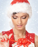 Portrait of a young woman opening a present. Portrait of a young and attractive Caucasian woman in a Santa hat opening a present. The image is taken on a light Stock Image