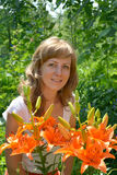 Portrait of the young woman with orange lilies Stock Photography