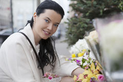 Portrait of young woman in outdoors flower-shop Royalty Free Stock Photography