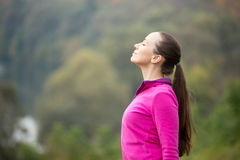 Portrait of a young woman outdoors in a sportswear, head up royalty free stock image