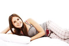 Portrait of young woman in pajamas laying in bed. Stock Image