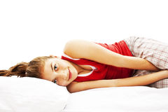 Portrait of young woman in pajamas laying in bed Royalty Free Stock Photography
