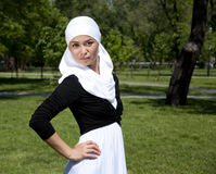 Portrait of young woman in park. With a white scarf on a head Royalty Free Stock Photography