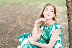Portrait of young woman in park in green dress royalty free stock photo