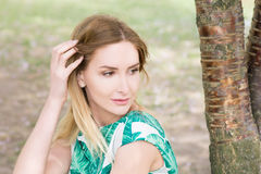 Portrait of young woman in park in green dress royalty free stock image