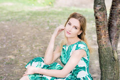 Portrait of young woman in park in green dress royalty free stock images