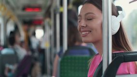 Portrait of a young woman passenger enjoying trip at the public transport, sitting with headphones in the modern tram. Portrait of a young woman passenger stock footage
