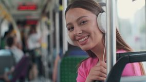 Portrait of a young woman passenger enjoying trip at the public transport, sitting with headphones in the modern tram. Portrait of a young woman passenger stock video