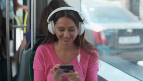 Portrait of a young woman passenger enjoying trip at the public transport, sitting with headphones in the modern tram. Portrait of a young woman passenger stock video footage