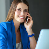 Portrait of a young woman on phone in front of a laptop computer. Royalty Free Stock Image