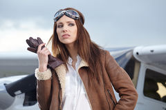 Portrait of young  woman pilot in front of airplane. Stock Images