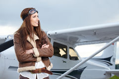 Portrait of young  woman pilot in front of airplane. Royalty Free Stock Photography