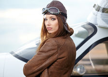 Portrait of young  woman pilot in front of airplane. Stock Photo