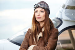 Portrait of young  woman pilot in front of airplane. Royalty Free Stock Photos