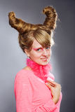 Portrait of young woman with pink plume. Over gray background. Woman with pink make-up Royalty Free Stock Images