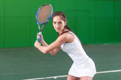 Portrait of a young woman playing tennis on court. Royalty Free Stock Photos