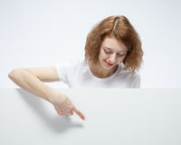 Portrait of young woman pointing on empty desk. You can add text Royalty Free Stock Image