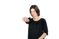 Portrait of young woman pointing in front of her. Against white background Stock Images