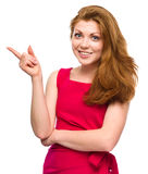 Portrait of a young woman pointing to the left. Using her index finger, isolated over white Royalty Free Stock Photography