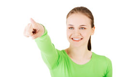 Portrait of young woman pointing up to the corner.  Royalty Free Stock Images