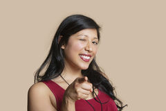 Portrait of a young woman pointing while winking over colored background Stock Photos
