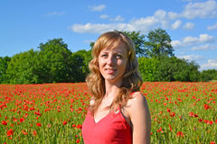 Portrait of the young woman in a poppy field Royalty Free Stock Photo