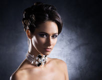 Portrait of a young woman in precious jewelry. Young, beautiful and rich woman in jewels of platinum and stones over luxury background Stock Photography