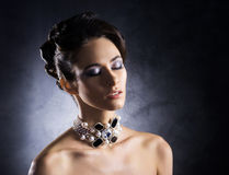 Portrait of a young woman in precious jewelry Royalty Free Stock Image