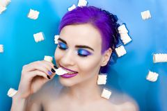 Portrait of young woman with purple hair in bath. Portrait of young woman female girl / fashion luxury model with purple hair and bright makeup relaxing in bath royalty free stock photos
