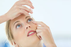 Portrait of young woman putting eye drops Stock Photos