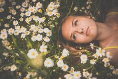 Portrait of young woman with radiant clean skin lying down amid flowers on a lovely meadow. On a spring/summer day stock photography