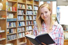 Portrait Of Young Woman Reading Book In Bookstore royalty free stock photos
