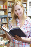 Portrait Of Young Woman Reading Book In Bookstore Stock Photos